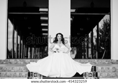 Big breasts brunette bride with wedding bouquet posed at wedding hall on the red carpet