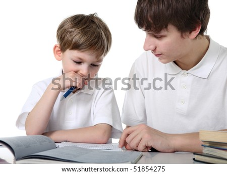 Big brother does lessons with younger brother - stock photo