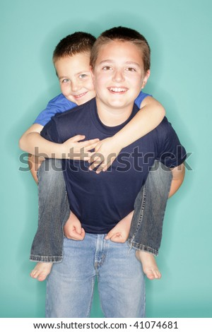 Big brother giving his little buddy a piggyback ride - stock photo