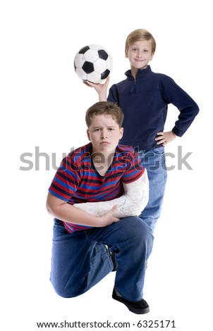 Big brother has a broken arm...so no soccer... Bonding, friendship, togetherness, love. - stock photo