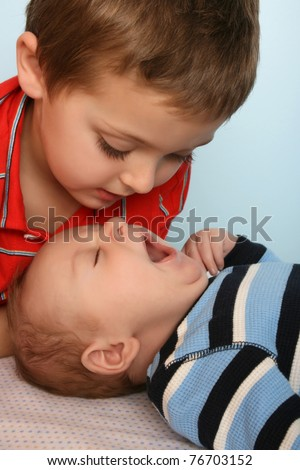 Big brother looking at his baby brother yawning - stock photo