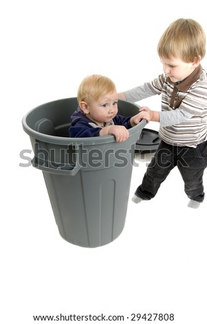 Big brother tries to get rid of little brother by putting him out with the garbage - stock photo