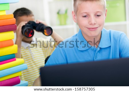 big brother watching something on the laptop, junior spy on him - stock photo