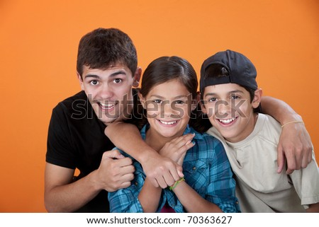 Big brother with two siblings smiling on orange background - stock photo