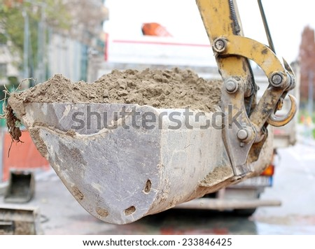 big bucket of a bulldozer and a truck in the background - stock photo