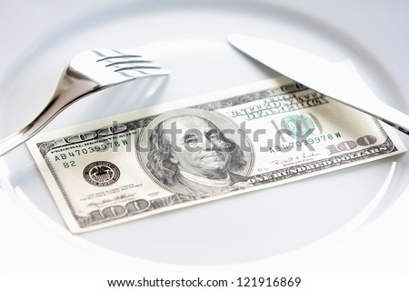 Big bucks/ One hundred american dollars bill on a white plate, with fork and knife. Buying power, money management, charity events & other in business, economy, finance, banking and everyday life. - stock photo