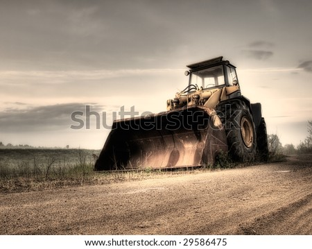 Big bulldozer at the building site.Monochrome toned.This portfolio contains color and B/W version of this image. - stock photo