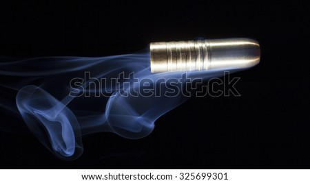 Big bullet that has smoke behind on a black background