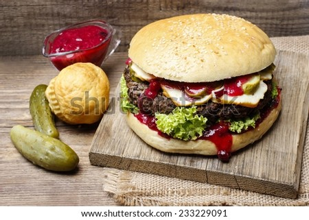 Big burger on wooden background - stock photo