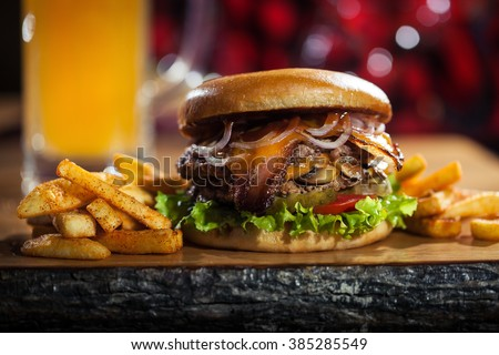Big burger with fries on the wooden table - stock photo