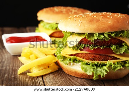 Big burgers on brown wooden background