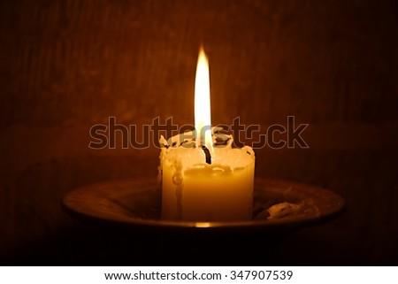 Big burning candle in a dim church - stock photo