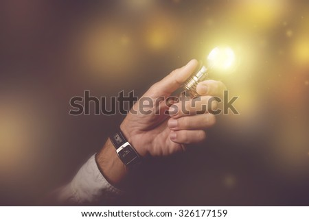 Big business idea visual metaphor, businessman with light bulb lightning up the dark office interior, retro toned image, selective focus. - stock photo