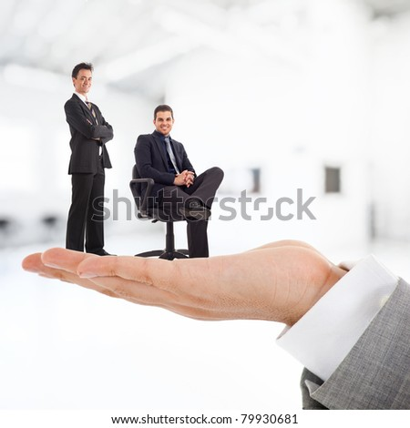 Big businessman holding businesspeople on his hand. - stock photo