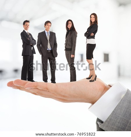Big businessman holding people on his hand. - stock photo