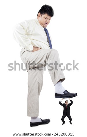 Big businessman trample a little businessperson, symbolizing business competition - stock photo