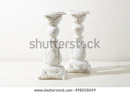 Big candleholders with original design stand on the whtie background
