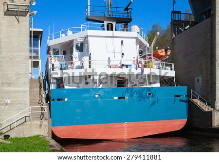 Big cargo ship comes to the narrow gateway of Tsvetochnoye lock on the Saimaa Canal, a transportation canal that connects lake Saimaa with the Gulf of Finland near Vyborg, Russia - stock photo