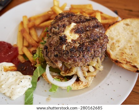 Big cheese hamburger with fries and salad served in BBQ restaurant - stock photo