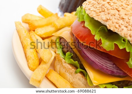 big cheeseburger garnished with french fries on a  plate and a glass of cola on white background - stock photo