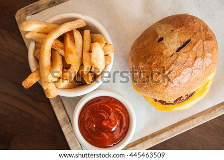 Big cheeseburger with melted cheese, fries and wood background. - stock photo