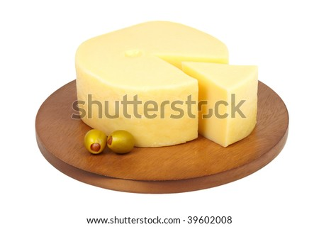 Big chunk of cheese with green olives on wooden cheeseboard.