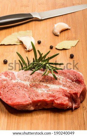 Big chunk of fresh meat on cutting board decorated with rosemary, pepper and garlic on the background - stock photo