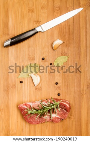 Big chunk of fresh meat on cutting board decorated with rosemary, pepper, garlic and bay leaf - stock photo