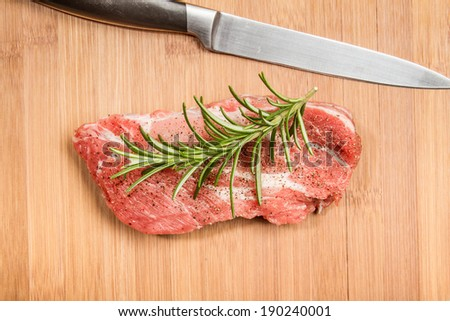 Big chunk of fresh meat on cutting board decorated with rosemary shot from the top - stock photo