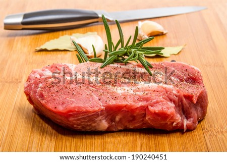 Big chunk of fresh pork steak seasoned with rosemary and pepper. Garlic and dried bay leaf on the background - stock photo