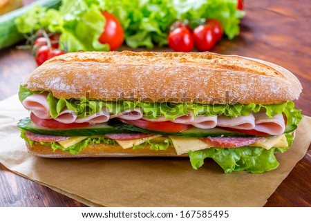 Big Ciabatta Sandwich with lettuce, slices of fresh tomatoes, ham, turkey breast and cheese - stock photo