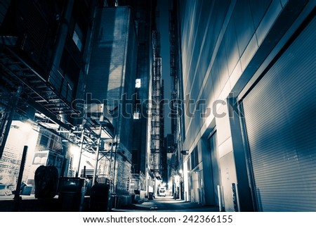 Big City Alley at Night. American Downtown Alley After Dark. Blue Color Grading. - stock photo