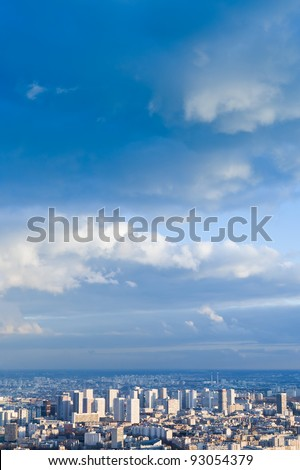 big city under high blue sky with white clouds - stock photo