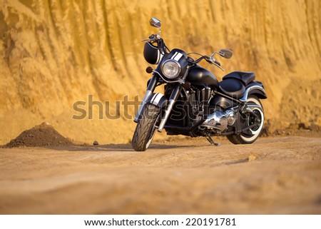 Big, clean, black and unknown chopper bike in desert - stock photo