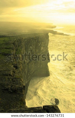 big cliffs and Atlantic ocean in Inishmore,the biggest island of Aran islands,Ireland yellow filter added - stock photo