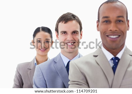 Big close-up of colleagues smiling in a single line with focus on the middle man - stock photo