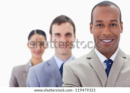 Big close-up of people dressed in suits smiling in a single line with focus on the first man - stock photo