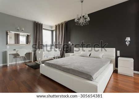 Big comfortable double bed in elegant classic bedroom - stock photo