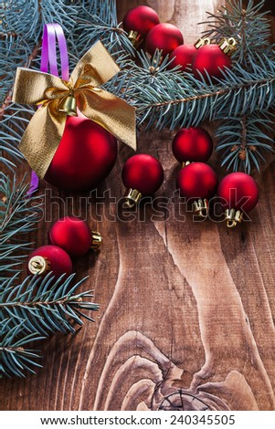 big composition of christmas toys red baubles gold colored bow and branches of fir tree on old wooden board with small copyspace - stock photo