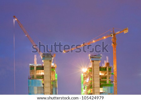 Big Construction Site with Working Cranes at dusk for Business Background - stock photo