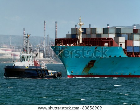 big container ship pulled by a tugboat into the port of algeciras - stock photo