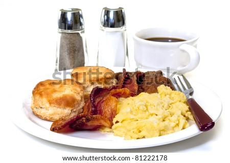 Big country breakfast with scrambled eggs, bacon, sausage, buttermilk biscuits, and coffee.  Salt and pepper shakers in background.  Isolated on white background. - stock photo