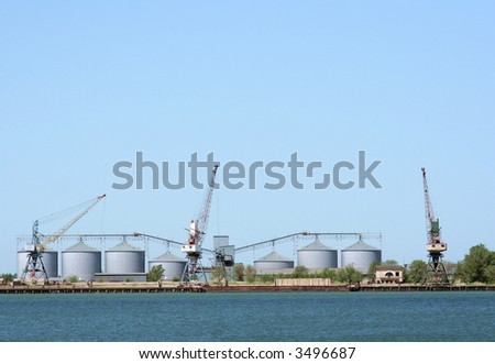 Big cranes and oil tanks in the seaport - stock photo