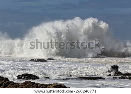 Big crashing wave against a rocky beach - stock photo