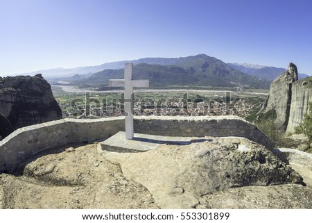 Big cross in front of stone masonry fence against mountain landscape background. Holy Trinity Meteora monastery, Thessaly, Greece.