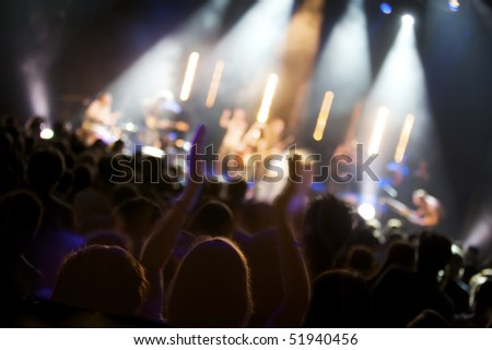 Big crowd of fans listening to live concert of pop band on stage, soft focus. - stock photo