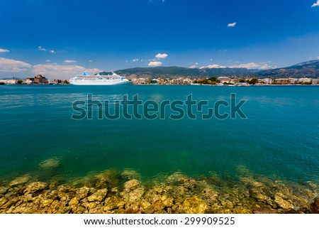 Big cruise ship anchored in port with turquoise waters in the foreground against a blue sky and clouds in Greece - stock photo