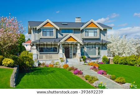 Big custom built luxury  home with nicely trimmed and landscaped front yard in the suburbs of Vancouver, Canada. - stock photo