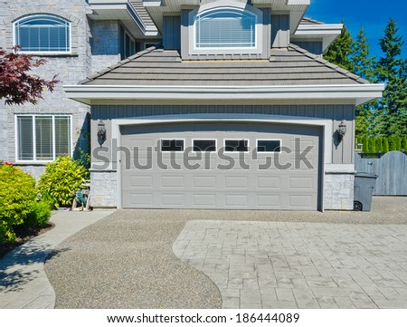 Big custom made double doors garage with nicely paved long and wide driveway in the suburbs of Vancouver, Canada. - stock photo