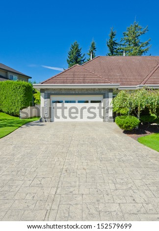 Big custom made double doors garage with nicely paved long driveway and trimmed bushes aside in the suburbs of Vancouver, Canada. - stock photo